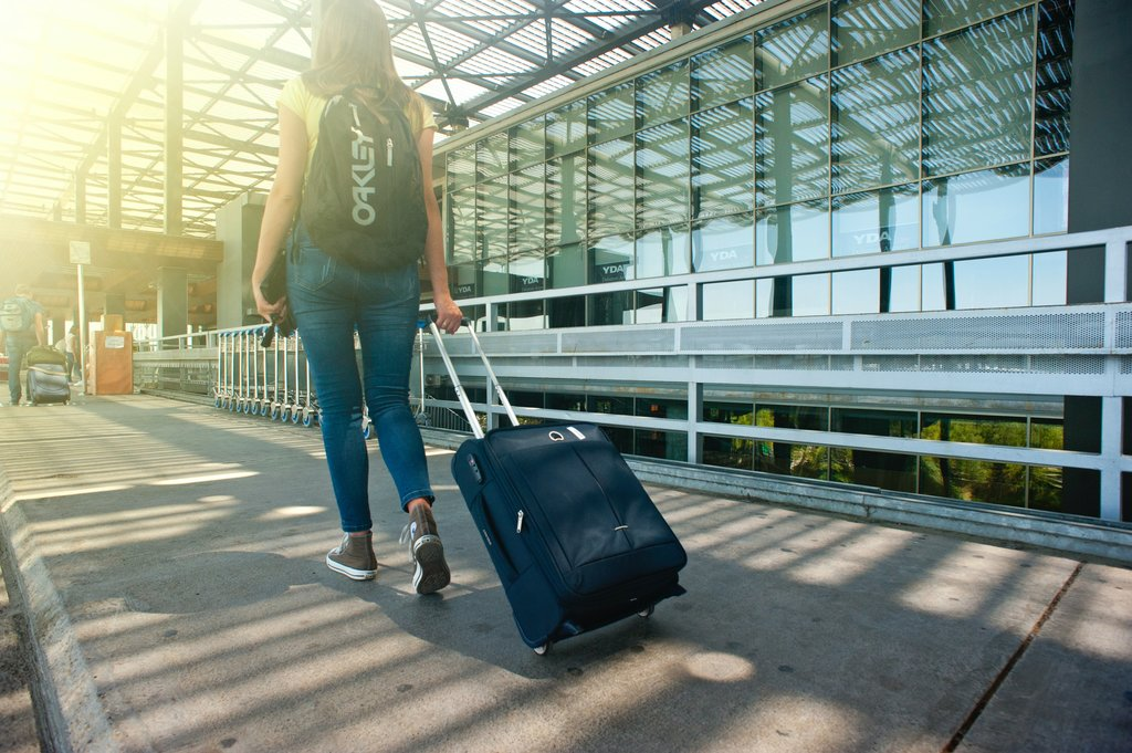 woman_walking_on_pathway_while_strolling_luggage
